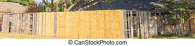 Panoramic view collapsed aged wooden fence near new lumber boards installation at suburban house in Texas, USA