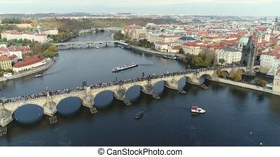 Panoramic view from above to the city of Prague and Charles Bridge, tourists on the Charles Bridge