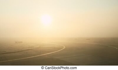 panoramic view from airplane window aircraft ride on empty runway against sunrise