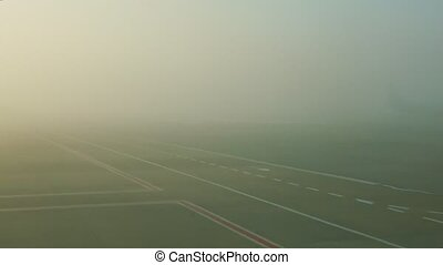 panoramic view from airplane window on empty runway against sunrise in fog