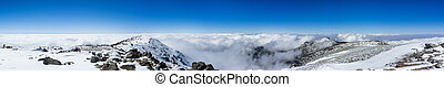 Panoramic view from the top of Mt San Antonio (Mt Baldy) on a snowy day; a sea of clouds in the background, Los Angeles county, southern California