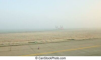 panoramic view from window airplane ride on empty runway against fields in fog