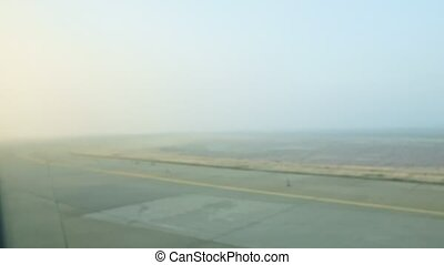 panoramic view from window airplane rides by empty runway against fields in fog