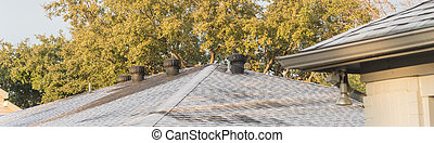 Panoramic view morning light and frost on black shingle roof of residential house near Dallas, Texas, USA