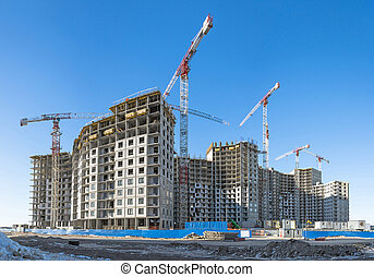 Panoramic view of a construction site with high cranes of apartment houses in microdistricts