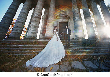 Panoramic view of a fairytale newlywed couple holding hands in front of old baroque ghotic church with columns at sunset