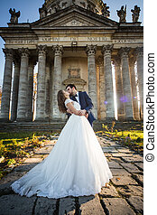 Panoramic view of a fairytale newlywed couple hugging and kissing in front of old baroque ghotic church with columns at sunset