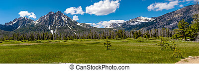 High mountains surround a grassy meadow