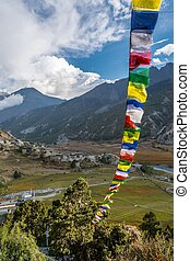 Panoramic view of a mountain valley with praying flags.