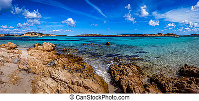Panoramic view of a rocky beach with clear colorful water