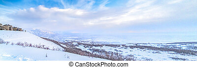 Panoramic view of a stunning snowy mountain against vibrant sky with clouds