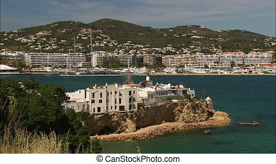 Wide low-angle panoramic still shot of limestone and coral-reef block apartments along the coastal beach, Spaniard Island buildings, and highland settlements facing the beach, Ibiza Island, Spain