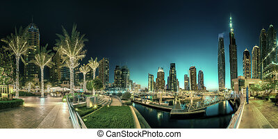 Panoramic view of Dubai Marina bay with yacht and cloudy sky...