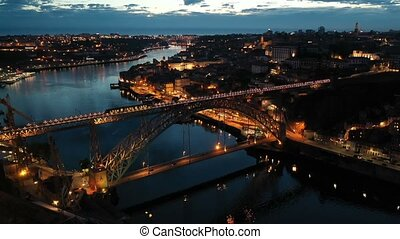 Night aerial view of Dom Luis I Bridge over Douro river against backdrop of lighted Porto city, Portugal