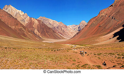 Panoramic view of mountain valley in the Andes with hikers