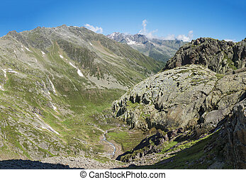 Panoramic view of mountain valley with winding stream of spring and snow-capped peaks at Stubai hiking trail, Stubai Hohenweg, Summer rocky alpine landscape of Tyrol, Stubai Alps, Austria