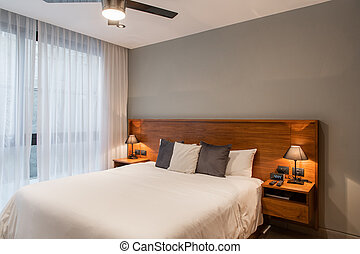Panoramic view of nice cozy bedroom with a big window