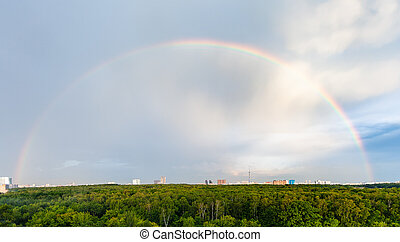 panoramic view of rainbow in blue cloudy sky