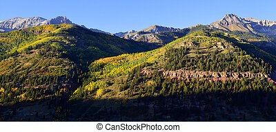 panoramic view of snow covered mountains and yellow aspen