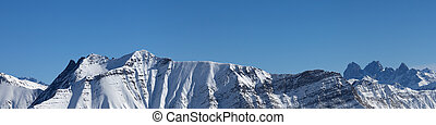Panoramic view of snowy mountains at sunny winter day