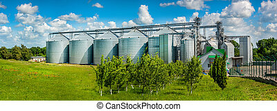 Panoramic view of storage of cereals, agro granary and sky with clouds. Agricultural business.