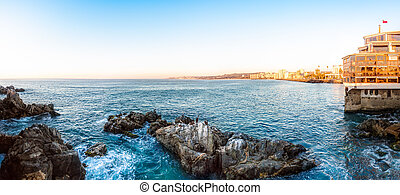 Panoramic view of the coastline in Vina del Mar, Chile with sea rocks on the foreground