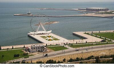 Panoramic View of the Ferris wheel revolves near the sea, traffic of cars on the road. Baku, Azerbaijan. Time Lapse