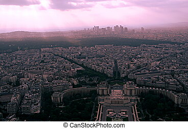 Panoramic view of the streets of Paris at the end of the afternoon, with the last sunbeams falling over the city, from the Eiffel Tower, on a very cloudy day