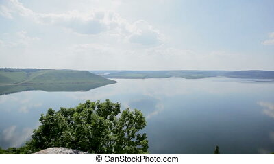 Panoramic view of the wide river with steep banks, forest, blue sky with white clouds reflected in the water. Aerial view