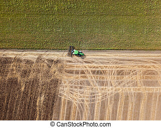 Panoramic view of tractor plowing the soil after harvesting on the field. Top view from drone.