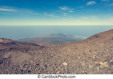 Panoramic view of volcanic landscape raising above sea level.