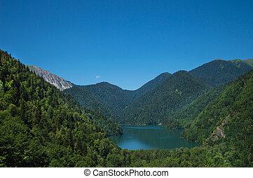 Panoramic view on mountain lake in front of mountain range.