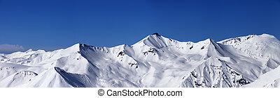Panoramic view on off-piste slopes and blue sky at nice day. Caucasus Mountains, Georgia, ski resort Gudauri.