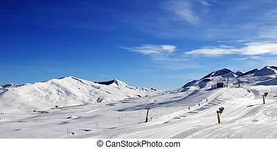 Panoramic view on ski slope with snowmaking at sun day....