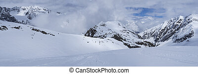 Panoramic view on winter mountain landscape at Stubai Gletscher ski area with snow covered peaks at spring sunny day. Blue sky background. Stubaital, Tyrol, Austrian Alps