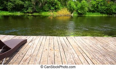Panoramic view on wooden pier with loungers and river in...