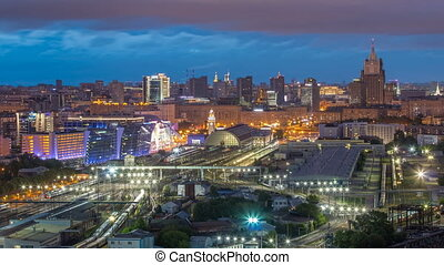 Panoramic top view to Kiev Railway Station night to day transition timelapse and modern city in Moscow, Russia. Aerial rooftop view with trains and rail tracks. Illuminated buildings