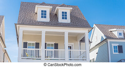Panoramic white painted porch with banister and dormer roof of two story houses near Dallas, Texas