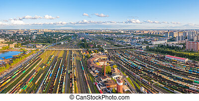 Panoramic wide view rail sorting freight station with various railway cars, with many rail tracks railroad. Aerial view heavy industry manufacturing cityscape.