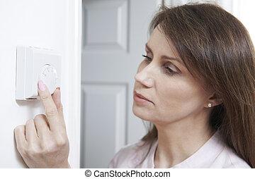 panowanie, kobieta, główny, termostat, regulując, ogrzewanie