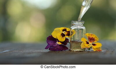 pansies essential oil in beautiful bottle on wooden White...