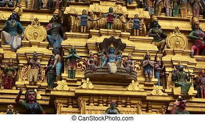 Sculpted and painted deities, displayed on the golden facade of a model temple on the altar of a real Hindu temple. 4k footage 2160p