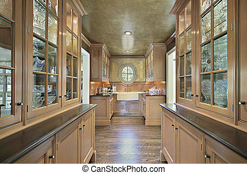 Pantry in luxury home with salmon colored cabinetry