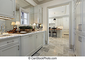 Pantry in luxury home with view into kitchen