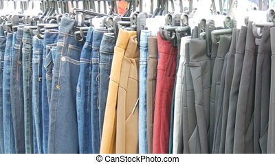 Pants hang on hanger, women look at clothes and choose. Flea...