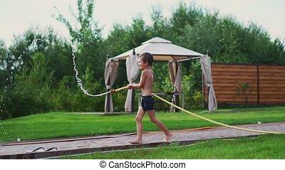 papa, lent, maman, famille, garçons, maison, motion., deux, eau, leur, tremper, rire, tuyau, arrière-cour, sourire, jouer, heureux
