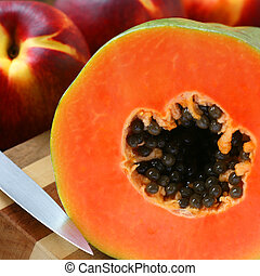 Papaya on Cutting Board - Cut papaya on cutting board with...