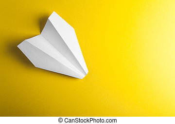 paper airplane on yellow background