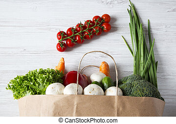 Paper bag of different vegetables on white wooden background. Healthy food. Top view. From above.