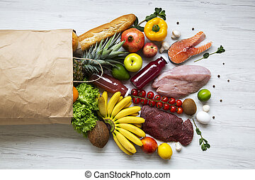 Paper bag of healthy products on white wooden background, top view. Health food. Flat lay. From above.